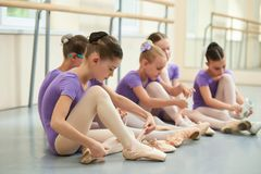 Baletnicza dziewczyna przystosowywa jej baletniczych buty Fotografia Stock