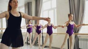 Baletniczy nauczyciel demonstruje nogi i ręki ruchy jej mali ucznie podczas gdy dziewczyny są wielostrzałowe po ona zbiory