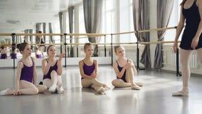 Baletniczy nauczyciel doświadczająca balerina demonstruje ruchy jej mali ucznie siedzi dalej tanczy na tiptoe zbiory