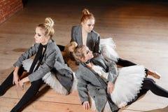 Baletniczy pojęcie Młode balerin dziewczyny relaksują obsiadanie na podłoga Kobiety przy próbą w białej spódniczce baletnicy i po Obrazy Stock