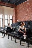 Baletniczy pojęcie Młode balerin dziewczyny siedzi na czerni krzesłach w sala Kobiety przy próbą w czerni Zdjęcie Royalty Free