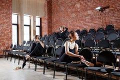 Baletniczy pojęcie Młode balerin dziewczyny siedzi na czerni krzesłach w sala Kobiety przy próbą w czerni Obraz Royalty Free