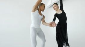 Baletniczy tancerz w bielu i balerinie podnosi atrakcyjnej baleriny w jej rękach, zakończenie na początku zbiory wideo