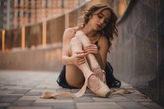 Balettdansör som sitter jordningen i pointeskor Huvudsaklig fokus på ben Royaltyfri Foto