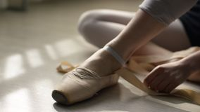 Balettdansören binder upp hennes pointes Balettdansör som binder balettskor, innan utbildning royaltyfria foton