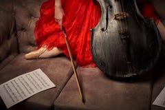 Balettdansören i röd klänning och pointe som spelar på antikvitet, svärtar violoncellen Royaltyfria Foton