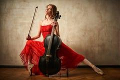 Balettdansören i röd klänning och pointe som spelar på antikvitet, svärtar violoncellen Royaltyfri Bild