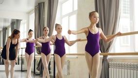 Balettläraren hjälper hennes lilla kvinnliga studenter med arm-, hand- och benpositioner under kurs i dansskola arkivfilmer