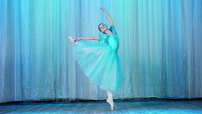Balettrepetition, på etappen av den gamla teaterkorridoren Ung ballerina i blåa balettklänning- och pointeskor, danser lager videofilmer
