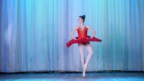 Balettrepetition, på etappen av den gamla teaterkorridoren Ung ballerina i röda balettballerinakjol- och pointeskor, danser lager videofilmer