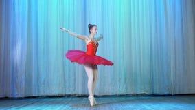 Balettrepetition, på etappen av den gamla teaterkorridoren Ung ballerina i röda balettballerinakjol- och pointeskor, danser stock video