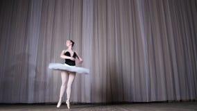 Balettrepetition, på etappen av den gamla teaterkorridoren Ung ballerina i vita balettballerinakjol- och pointeskor, danser lager videofilmer