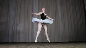 Balettrepetition, på etappen av den gamla teaterkorridoren Ung fet ballerina i vita balettballerinakjol- och pointeskor, försök lager videofilmer