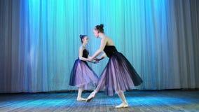 Balettrepetition, på etappen av den gamla teaterkorridoren Unga ballerina i eleganta klänningar för lilasvart och pointeskor lager videofilmer