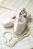 Balettskor och pärlemorfärg halsband på musikaliska anmärkningar Royaltyfria Foton