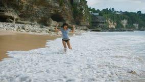 Bali östrand Brunettleendet stöter ihop med sanden på stranden och kyler din fot i vattnet Tycka om för kvinna arkivfilmer