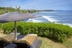 bali Индонесия Кровати под зонтиком пляжа обозревая море на краю скалы стоковое фото