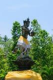 bali Индонесия 6-ОЕ ОКТЯБРЯ 2018 Традиционная скульптура бога Бали покрытая с юбкой перед голубым небом и зелеными деревьями стоковая фотография rf