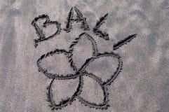 Bali-Aufschrift und Frangipaniblume gezeichnet auf schwarzen Sand lizenzfreie stockbilder