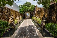 Bali bana som fodras med traditionella statyer och växter arkivbilder
