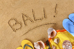 Bali beach. Beach background with towel and flip flops and the word Bali written in sand Stock Image
