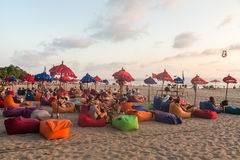 Bali beach bar. BALI, INDONESIA - OCTOBER 31, 2015: Tourists enjoy a drink while watching the sunset in a beach bar along Seminyak beach, just north of Kuta, in Royalty Free Stock Photo