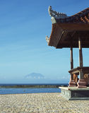 Bali Beach House Indonesia. View of a dormant volcano from a Bali beach house. In the distance, a woman scours the shallows for clams stock photography