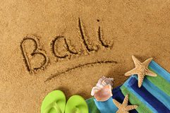Bali beach. The word Bali written on a sandy beach, with beach towel, starfish and flip flops royalty free stock images