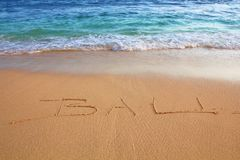 Bali on the beach. Bali written in sand on beach with small wave stock photography