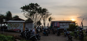 BALI, BERAWA BEACH, INDONESIA MARCH 2017: Local beach bar `Naked Coconut` at sunset time from car park with many scooters & beach Stock Photo