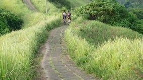 Bali: Bicicleta da equitação do homem através do campo de grama video estoque