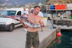 Bali, Eiland Kreta, Griekenland, - 30 Juni, 2016: De mens is een visser draagt een grote vis sawfish Royalty-vrije Stock Fotografie