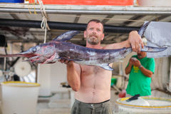 Bali, Eiland Kreta, Griekenland, - 30 Juni, 2016: De mens is een visser draagt een grote vis sawfish Royalty-vrije Stock Foto's