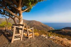 Bali, Eiland Kreta, Griekenland, - 25 Juni, 2016: Mooi ochtendlandschap met twee houten banken dichtbij de boom De banken zijn in Stock Foto's