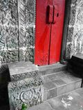 Bali house with red door & stone carved walls Royalty Free Stock Images