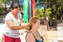 BALI, INDONÉSIA - 14 DE ABRIL DE 2017: A mulher superior está obtendo a massagem principal na praia foto de stock