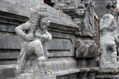 BALI, INDONÉSIA - 13 DE DEZEMBRO DE 2017: suporte cinzelado da estátua fora da entrada ao templo hindu imagem de stock
