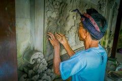 BALI, INDONÉSIA - 8 DE MARÇO DE 2017: Homem que usa um formão para fazer a arte em uma parede do cimento, em Denpasar Bali encont Foto de Stock Royalty Free