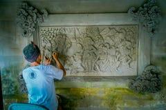 BALI, INDONÉSIA - 8 DE MARÇO DE 2017: Homem que usa um formão para fazer a arte em uma parede do cimento, em Denpasar Bali encont Fotos de Stock Royalty Free