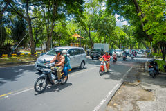 BALI, INDONÉSIA - 8 DE MARÇO DE 2017: Povos não identificados que conduzem motocicletas e carros na estrada completamente do tráf Imagem de Stock