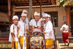 BALI, INDONÉSIA - 3 DE OUTUBRO DE 2018: Meninos do Balinese no traje tradicional e no homem europeu que controlam um zangão em um imagem de stock