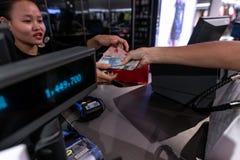 BALI, INDONÉSIA - FEBRAURY 19, 2019: Jovem mulher que dá o dinheiro ao caixa na loja da forma foto de stock royalty free