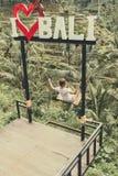 BALI, INDONÉSIE - 23 JANVIER 2018 : Jeune femme sur l'oscillation dans la jungle Oscillation tropicale de paradis bali Photographie stock libre de droits