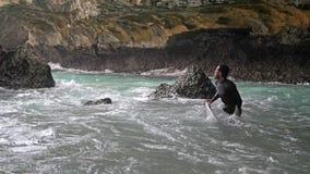 Bali, Indonésie, le 21 juin 2018 Le surfer avec le conseil sortent de l'océan entre les roches Mouvement lent 3840x2160 clips vidéos