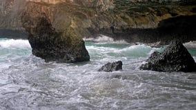 Bali, Indonésie, le 21 juin 2018 Le surfer avec le conseil sortent de l'océan entre les roches Mouvement lent 3840x2160 banque de vidéos