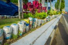 BALI, INDONÉSIE - 8 MARS 2017 : Bouteilles d'eau en plastique en parc à l'envers dans la rangée, réutilisée pour orner des parcs  Photos stock