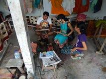 BALI, INDONESIË - CIRCA 2014: Een arbeider van de batikworkshop toont een toerist hoe te om te maken een battic ontwerp op een st Stock Foto's