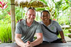 Bali, Indonesië - Maart 22, 2018: Cucasianmens en zijn bestuurder die bij camera glimlachen stock afbeeldingen