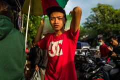 Bali, Indonesië - Maart 22, 2018: Een jonge Indonesische mens die aan markt in Ubud werken stock fotografie