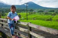 Bali, Indonesië - Maart 30, 2018: Jonge Aziatische jongen die camera bij de Tegallalang-Rijstterrassen bekijken stock foto's